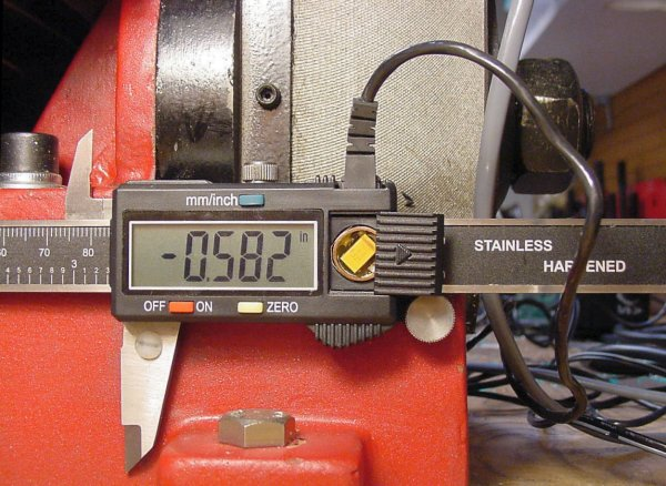 Digital caliper affixed to a milling machine using an external power supply through the data cable with a capacitor replacing the battery.