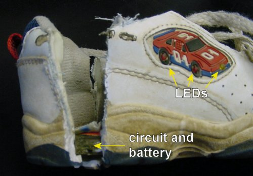 Light-up shoe with LEDs is cut open to reveal a circuit in the heel of the sole