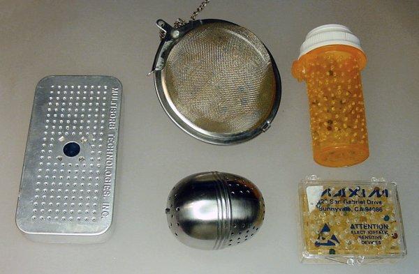 Silica gel beads in various containers such as a commercial aluminum perforated box, tea balls, and plastic containers with holes drilled in them.