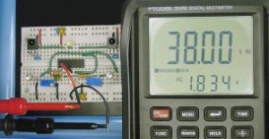 Infrared obstacle detector circuit implemented on a solderless breadboard and tuned using a multimeter with frequency display.