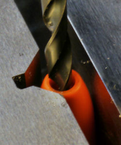 V groove holds banana cover while enlarging hole for lower gage wire