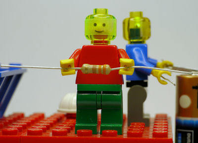 Lego minifig holding resistor in hands