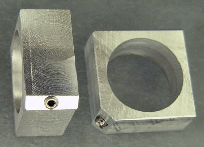 A square of aluminum with a motor hole drilled in the middle and a setscrew in the corner.