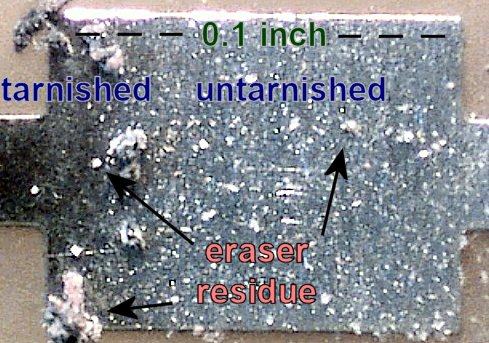 Large and small eraser residue from Pink Pearl removing tarnish from a PCB pad (60x magnification).