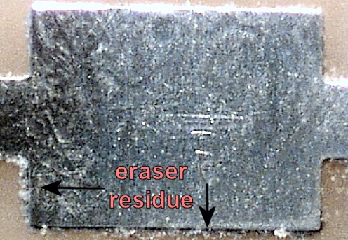 After rubbing the board with fingers, the smaller eraser residue is deposited on the pad edges and cracks (60x magnification).