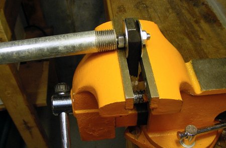 The front and back flat square jaws of the vise securely hold one end of the bent screw while force is applied by a steel pipe.