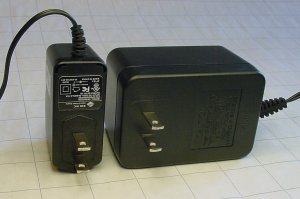 A modern commercial ac adapter switching power supply (left side) is cheaper, smaller, lighter, better oriented, and more efficient than the previous generation of linear wall warts (right side).