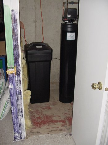 Brine tank and water softener in a basement closet.